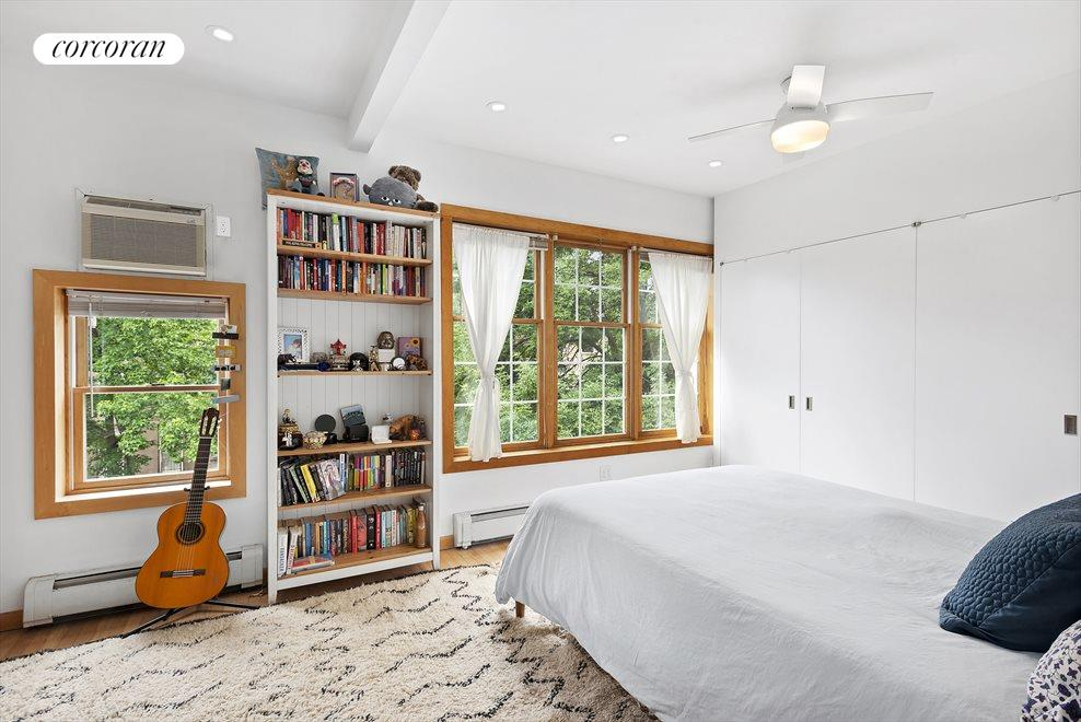 Large bedroom looks out over treetops
