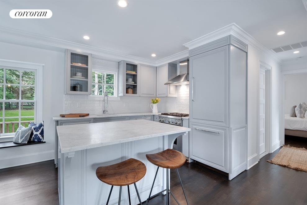 Open layout kitchen with carrera marble, custom cabinets, and Thermador appliances