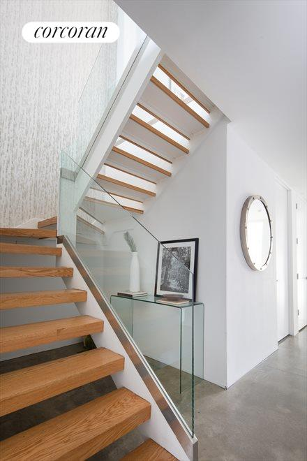 A sleek staircase with glass handrail