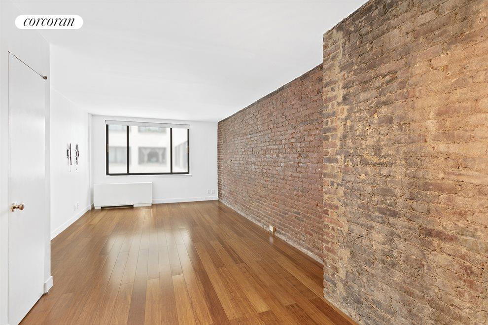 Spacious Living Room with exposed brick wall.