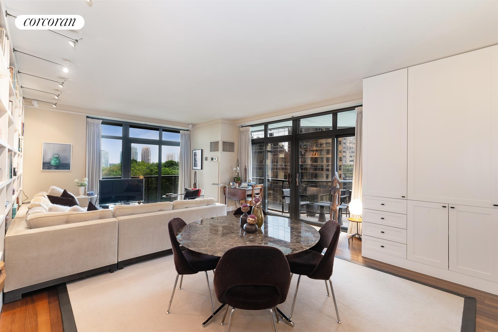 Fully renovated custom designed corner 2 bedroom, 2 bathroom with wrap balcony at 100 United Nations Plaza, one of Midtown Easts premiere white-glove condominiums.  Upon entering unit 9B at 100 United Nations Plaza you will pass through a welcoming foyer that leads to the spacious corner living and dining room with floor-to-ceiling windows and sliding glass doors that open out to the wrap-around balcony. Whether entertaining guests or having a quiet night in, enjoy picturesque views to the East River and overlooking the UN Gift Garden, as well as the city skyline to the south. A wall of custom built-in bookshelves with accent lighting and large built-in storage unit round out this inviting living space. The adjacent windowed kitchen has been gorgeously renovated and features warm, figured walnut cabinetry, quartz countertops and a classic subway tile backsplash with a suite of stainless steel appliances from Bosch. The generously sized, south-facing master bedroom suite boasts three large closets including a walk-in, custom built-ins and track lighting. The en suite master bathroom has been elegantly finished with floor-to-ceiling tile, marble floors, dual sink marble-topped vanity, recessed lighting, an extra-large walk-in shower with sliding glass doors and Cesana hardware, with fittings and fixtures from Toto and Waterworks. The sizeable second bedroom, found on the opposite side of the apartment from the master suite, has an eastern exposure as well as its own renovated en suite bath finished in a crisp white palette with floor-to-ceiling subway tile, pedestal sink and Jacuzzi bathtub.Measuring approximately 1,337 square feet, additional features of this polished home include roasted oak hardwood floors throughout, custom built-out closets, abundant storage space, separate laundry room complete with a utility sink and side-by-side washer and dryer, central heat and A/C, and custom mahogany wood flooring on the outdoor balcony.Located on East 48th Street and Firs