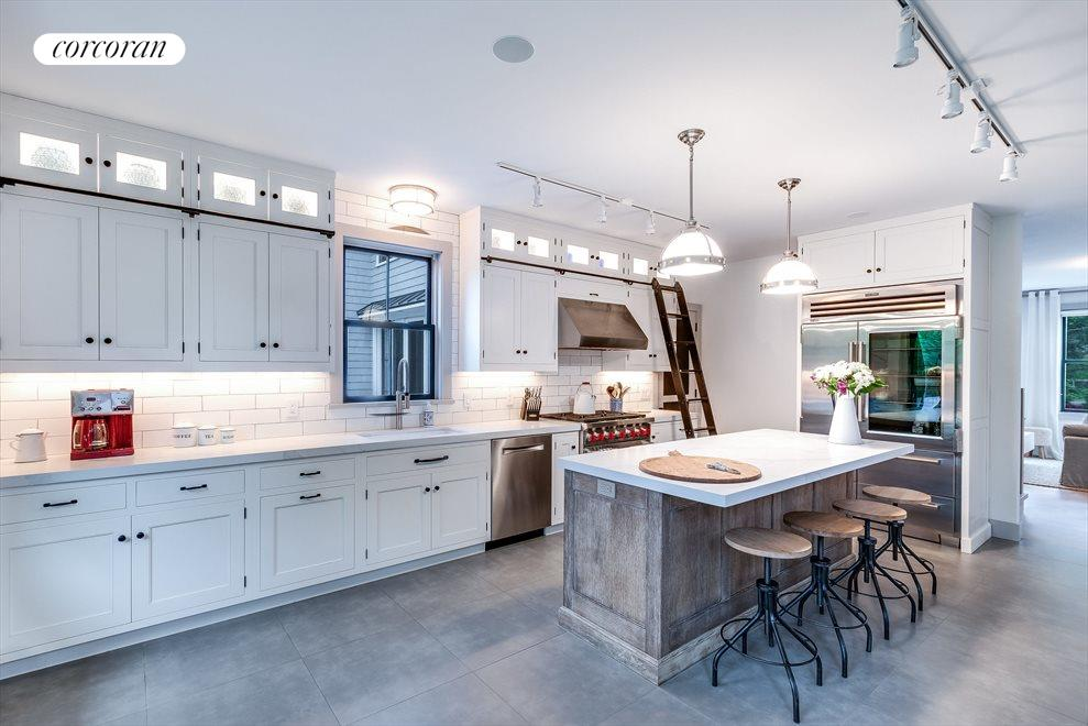 Large custom kitchen with high end appliances and breakfast counter