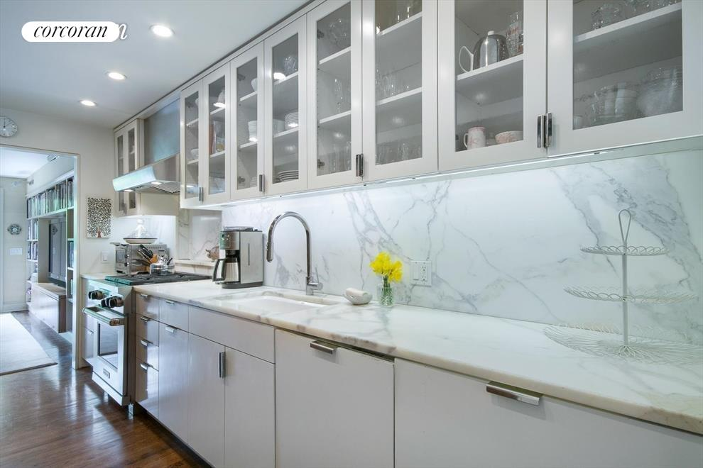 Long, beautifully appointed marble galley kitchen.