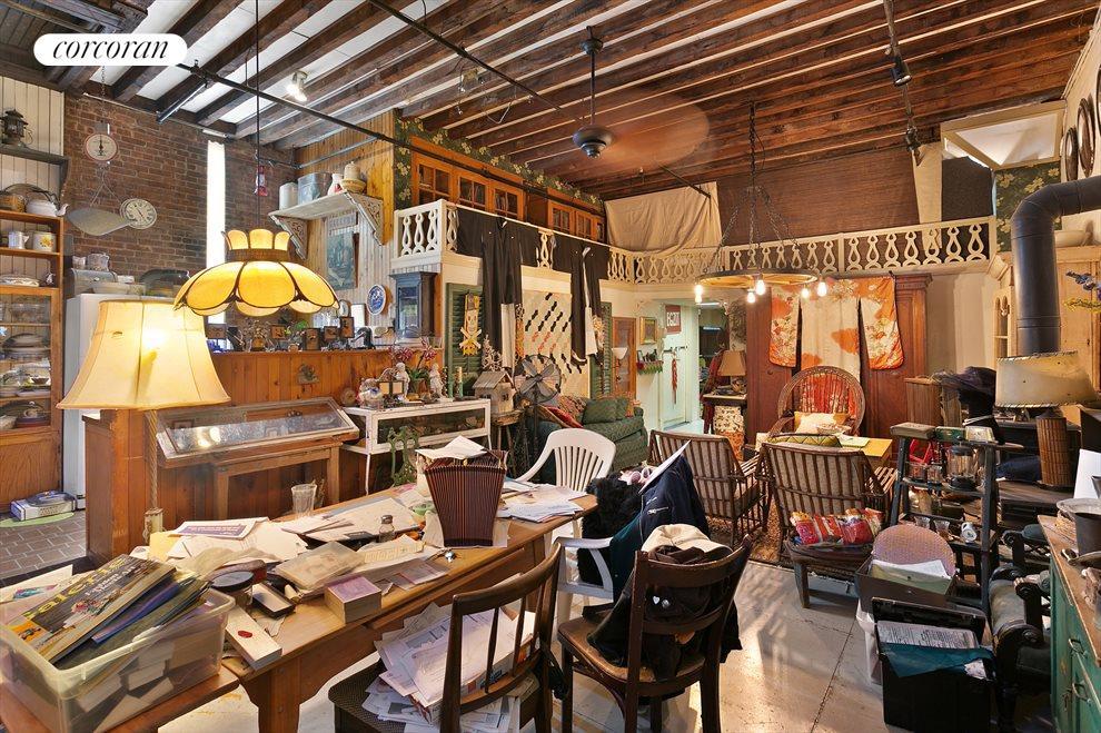 Mezzanine set up in living room with beams & brick