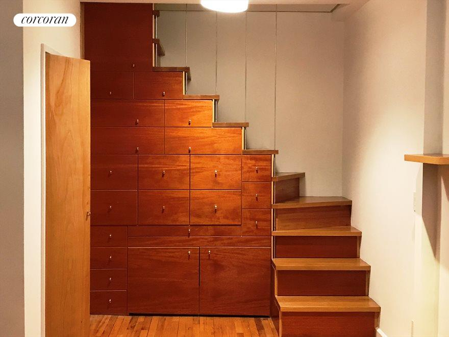 Storage wall with hidden desk and bed