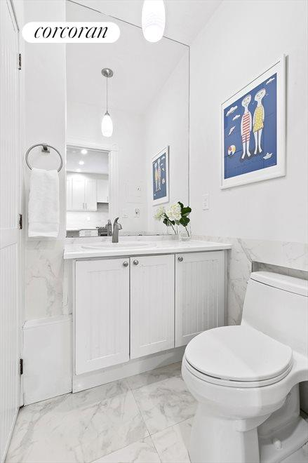 This powder room also houses the washer & dryer.