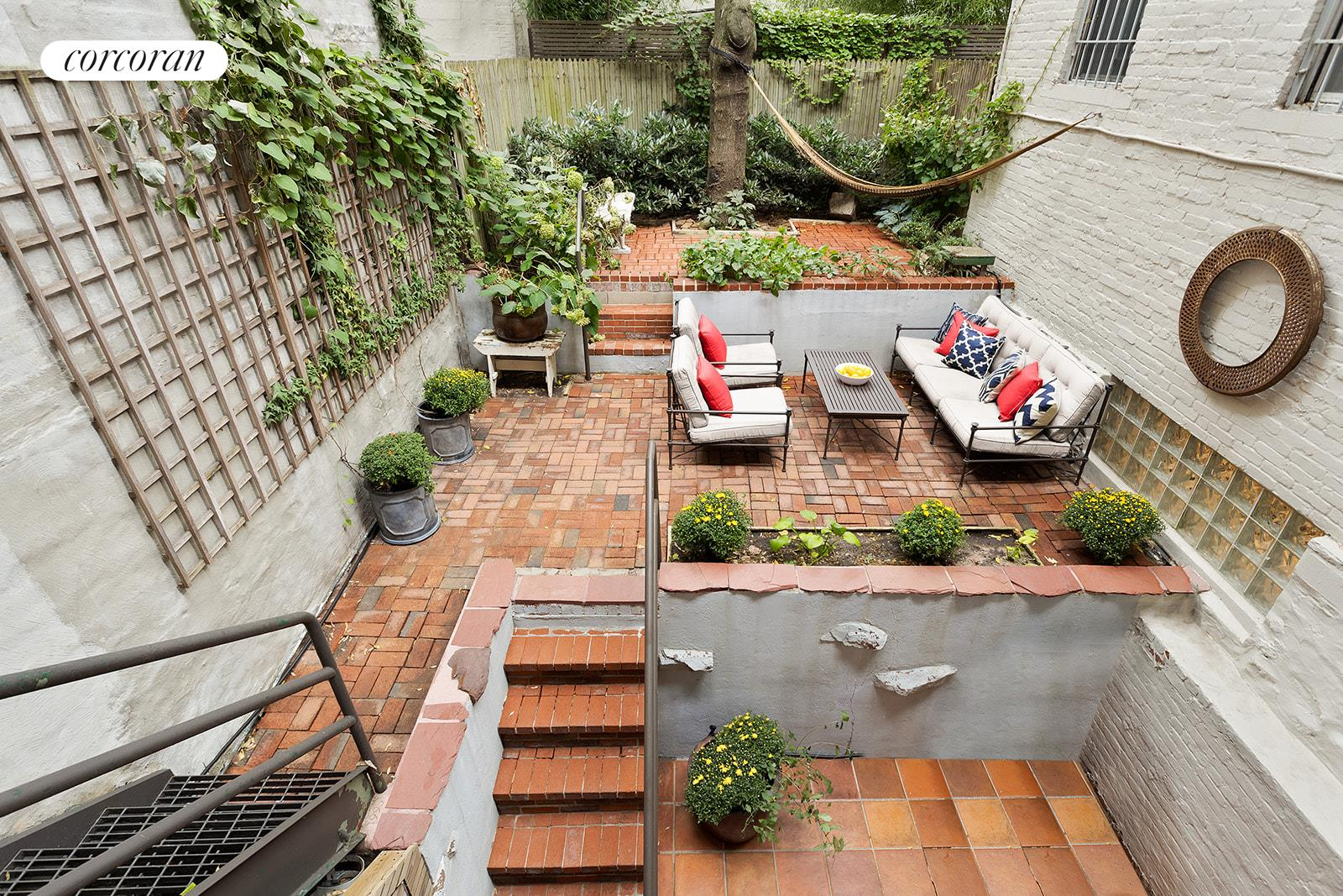 Back on the market! URBAN OASIS...WITH THREE-TIERED PRIVATE GARDEN ~ Looking for a spacious and tranquil home with sprawling outdoor space in Manhattan? You've found it. 425 East 9th Street #1A is a huge duplex coop (approximately 1200 interior square feet) that boasts a highly-coveted garden sanctuary in the heart of the East Village. Offering open-air serenity spread over three levels of exclusive backyard -- this exceedingly rare space is ideal for gardening, al fresco dining, lounging in a hammock and getting together with friends. Off the garden, enter into the oversized newly-renovated dining area on the lower level of the apartment, complete with abundant cabinet storage, stone countertops, luscious backsplash, walk-in pantry and white-washed exposed brick. There is also a useful media room on this level that could be used in a variety of ways, as well as a bathroom and a large closet that extends under the staircase. Upstairs, find a large living area that could be configured as another bedroom if so desired. This beautiful room includes enviable storage space, a built-in window seat overlooking the lush garden, a balcony with staircase down to the garden and a built-in work space with desk, bookshelves and drawers. The top-floor also holds the main bedroom with its own built-in closet. The top-floor full bathroom offers spa-like features: an expansive walk-in shower and plenty of storage space. Throughout the home, you'll find unique original details: gorgeous arched doorways with rich wood frames, sound-reduction flooring and exposed brick. Unit 1A is a legal one bedroom apartment currently being used as a two bedroom. 425 E. 9th Street is an eight-unit coop that offers central laundry and bike storage. Enjoy the ease of having top-notch restaurants, boutique shopping and Tompkins Square Park right on your doorstep. Pets welcome (cats OK / dogs upon board approval).
