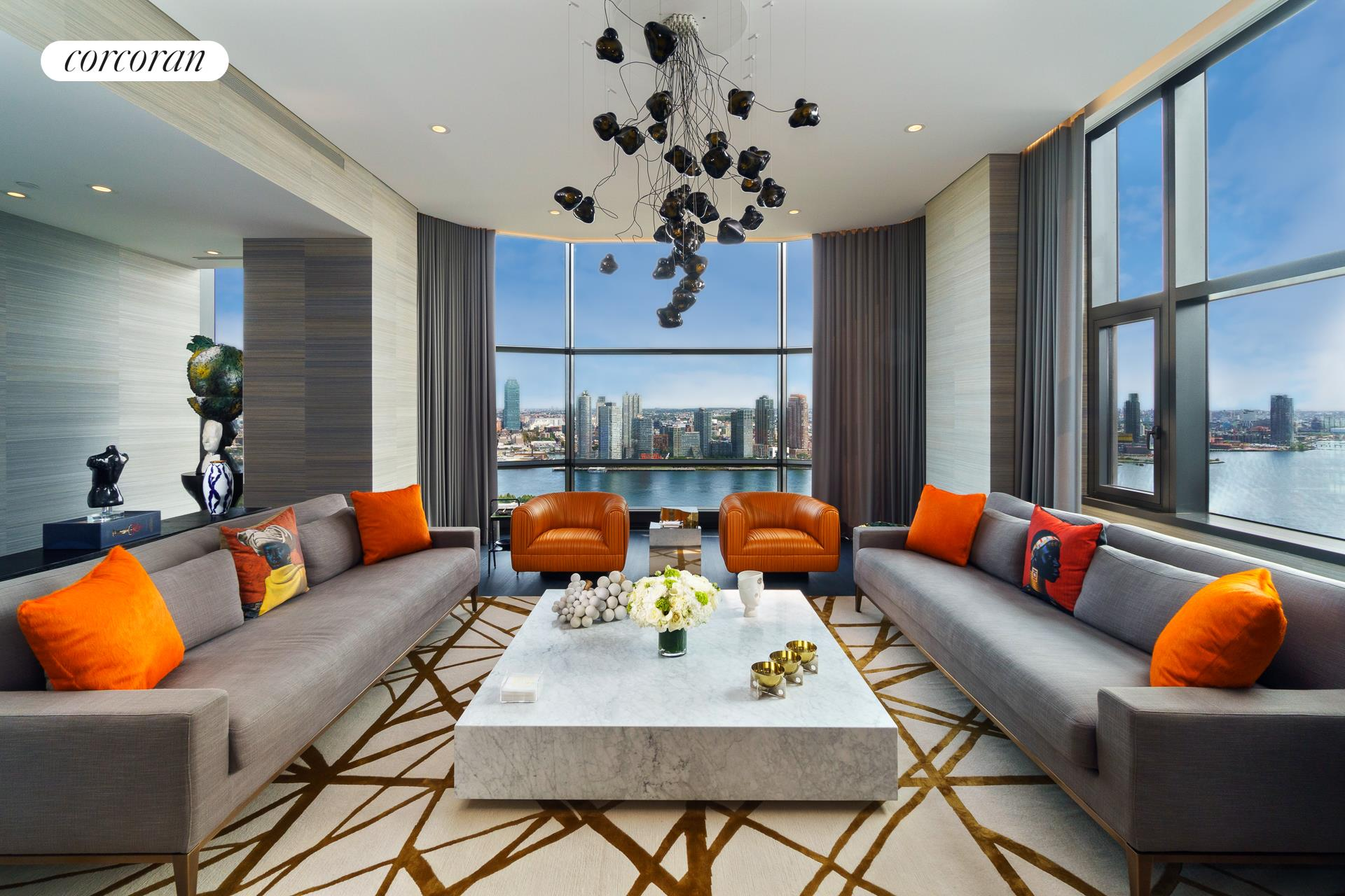 """This stunning, sun-drenched corner three bedroom, three bathroom luxury condominium has panoramic sweeping views of the East River, the United Nations, and the Empire and Chrysler buildings. Spanning approximately 2,609 square feet, this luxurious Foster + Partners designed home has ceilings up to 11'3"""", solid white-oak floors, Duravit fixtures, Dornbracht fittings, multi-zone central air conditioning with a thermostat in every room, motorized shades, a custom lighting system and a Sonos sound system. In addition there is a Savant Home Automation system that controls the various components. The residence has been beautifully decorated by renowned interior designer Robert Bowen and a parking space with valet parking transfers with the sale.  Off a semi-private elevator landing is an elegant entrance foyer that opens into a grand corner living room that is 24'3"""" by 20' and has eastern and southern exposures. This magnificent room has a wall of floor-to-ceiling bay windows which showcase the breathtaking views of the river. Adjacent, through pocket doors, is the south-facing formal dining room which also overlooks the river and provides a magnificent space for gatherings. The kitchen is superbly outfitted with Poliform white lacquer cabinetry and honed absolute black granite countertops. It is equipped with top-of-the-line appliances including a Subzero refrigerator with two freezer drawers, a Subzero wine refrigerator, a Miele oven and five burner range, a Miele microwave/convection oven, a Miele dishwasher, and a Miele warming drawer. There is also a laundry area with a Miele washer and dryer.  The extraordinary corner master bedroom suite faces south and west and has mesmerizing views of the iconic Manhattan skyline. The suite features an incredible dressing room that is 19'3"""" long as well as a separate walk-in closet; both have custom cabinetry and lighting. The lavish windowed en-suite master bathroom is clad in Sivec white marble with a Foster + Partners custom t"""