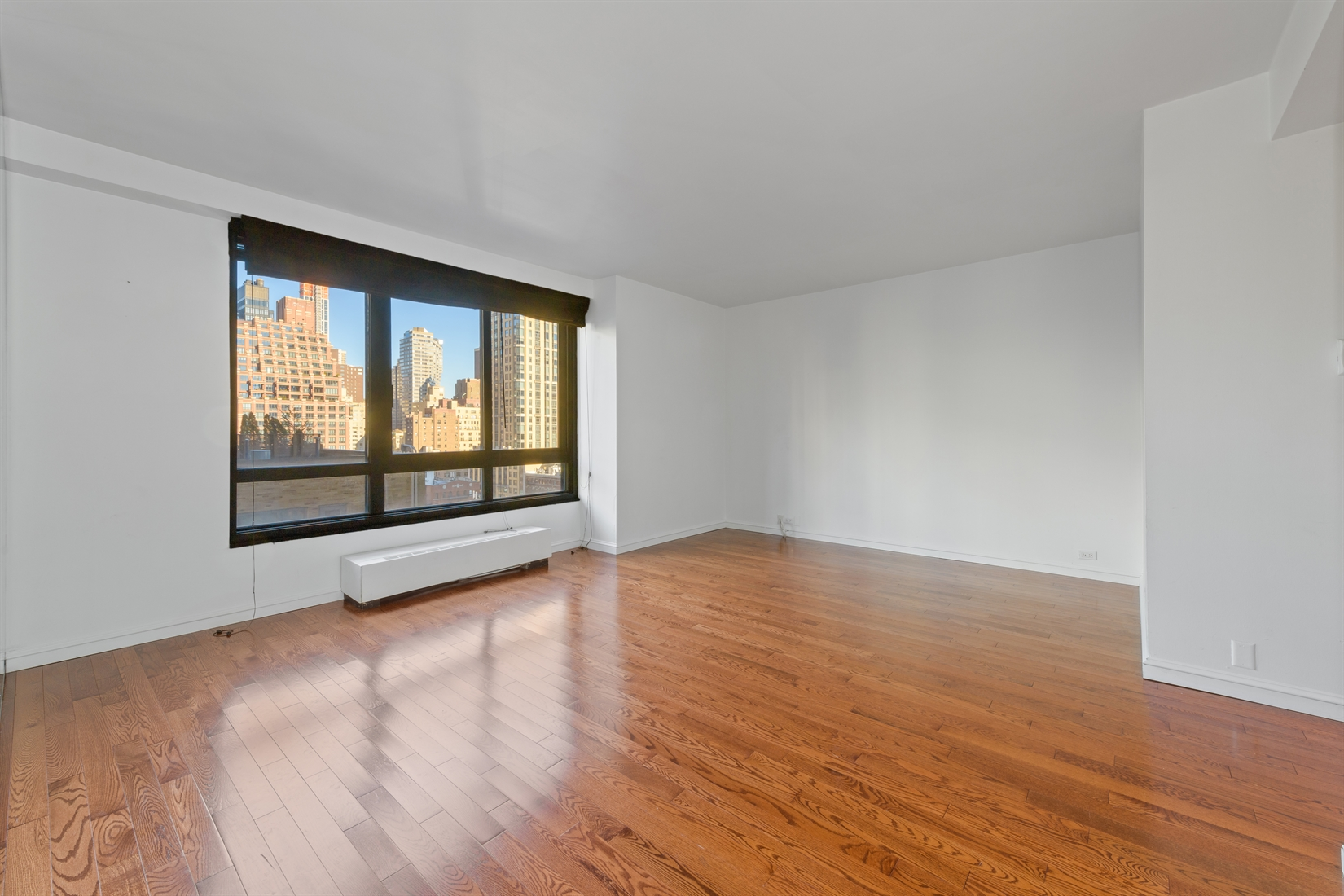 Spacious 1 bedroom, 1 bathroom with northern city views available for rent at 100 United Nations Plaza, one of Midtown East's premier white-glove condominium buildings.This bright and functional unit has beautiful wood flooring, great closet space and an updated kitchen. The extra-large living room has a separate alcove that is ideal for use as a dining area or work space, while over-sized north-facing windows highlight open skyline views. The updated galley kitchen has marbled floor and backsplash tile, a 5-burner gas range from Samsung, Haier stainless steel fridge and a full size dishwasher. The bedroom is also north-facing and will comfortably accommodate a king-size bed, and the en suite marble bathroom has a jacuzzi bathtub. Additional features include 3 extra-large closets, 9' ceilings, and central heat and A/C.Located on East 48th Street and 1st Avenue, 100 United Nations Plaza is a full service, white-glove condominium in Manhattan's Turtle Bay neighborhood. Residents are greeted with beautifully landscaped gardens and waterfalls and this impeccably run building offers a 24-hour doorman, valet and concierge service, on-site management office, renovated lobby and resident's lounge, common laundry room, fitness center and direct access to a 24-hour attended parking garage. Conveniently located to transportation and many great neighborhood shops and restaurants. Condominium application required. Showing by appointment only.