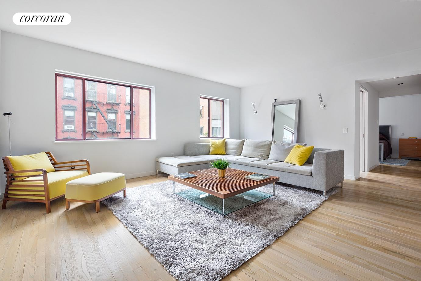 New to Alphabet City in the vibrant East Village and just steps from Tompkins Square Park is this gracious 1,054 square foot 2 bedroom, 2 bathroom CONDOMINIUM at 217 East 7th Street, 4CD. Recently gut renovated to the highest of standards, this spacious half-floor home enjoys a large L-shaped living/dining room that spans 22' and is graced with two oversized south-facing windows allowing tons of natural light to flow throughout the home. You'll also notice beautiful hardwood floors and a dedicated dining area that can comfortably accommodate a large dining table. An open windowed kitchen boasts a suite of top-of-the-line appliances including Subzero refrigerator, Subzero wine storage, Viking 4-burner gas stove, Miele dishwasher, and Viking built-in microwave. Caesarstone counters and backsplash, custom matte black cabinetry, and a large breakfast bar with floating glass cabinet complete the space. A spacious gallery with custom built-in shelves leads you into both bedrooms. The primary bedroom comfortably accommodates king size furniture and enjoys a large walk-in closet with a full-size Miele washer/dryer, and a beautifully appointed ensuite bathroom replete with Kohler fixtures throughout. The second bedroom, currently configured as a home office, is graced with an abundance of natural light and bright south exposures.Finally, the home is replete with high efficiency 3-zone HVAC, LED lighting, pocket doors throughout, unique soffits which conceal window treatments, and a Siedle video intercom system. 217 East 7th Street is a boutique condominium with a roof deck, video intercom, bike room, exercise room, and only 2 apartments per floor in the very heart of the East Village and just a stone's throw from a slew of restaurants, bars, cafes, and the best of Tompkins Square Park. Pets welcome.