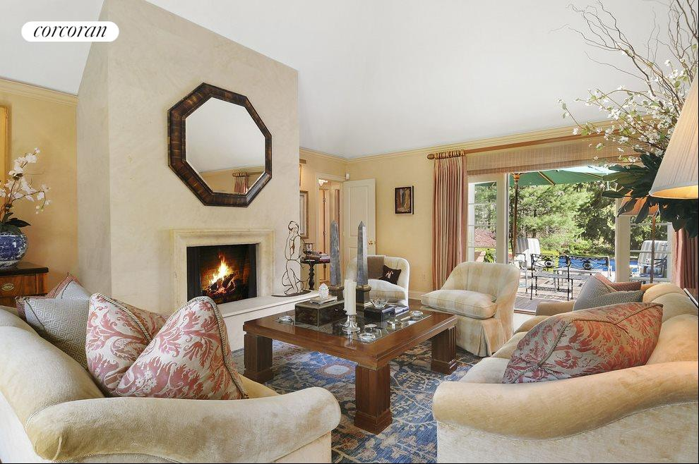 Living room with fireplace opens on to beautiful deck and gardens