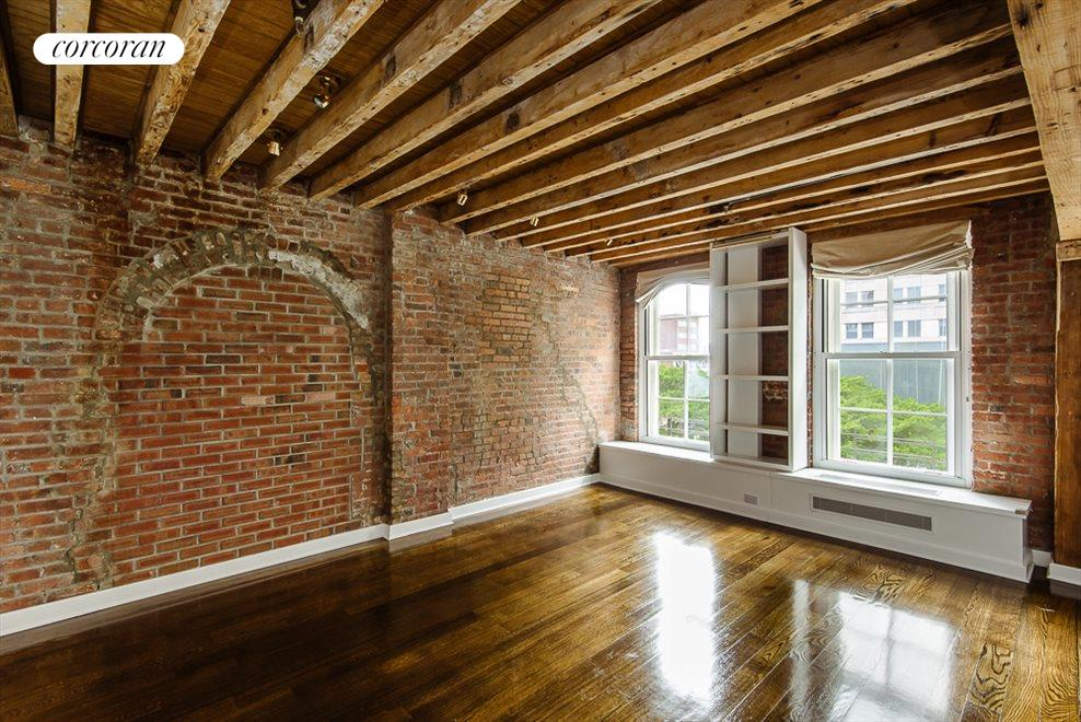 Master Bedroom with Brick Wall and Beamed Ceilings
