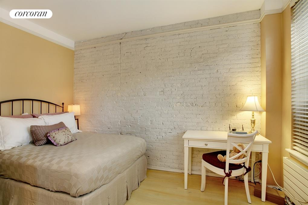 Sleeping area with exposed brick wall, separate AC