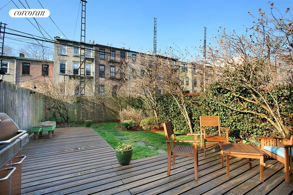 Deep landscaped garden with large wood deck