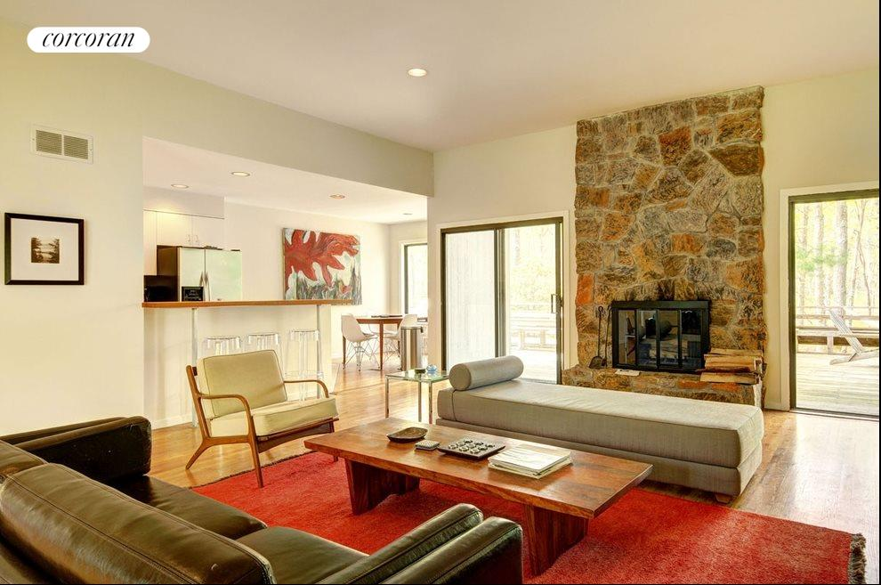New York City Real Estate | View 18 Shorewood Drive | Main living room with central fireplace and view toward open kitchen and dining area