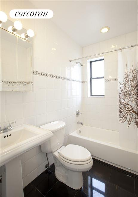 Tastefully renovated windowed bathroom with marble