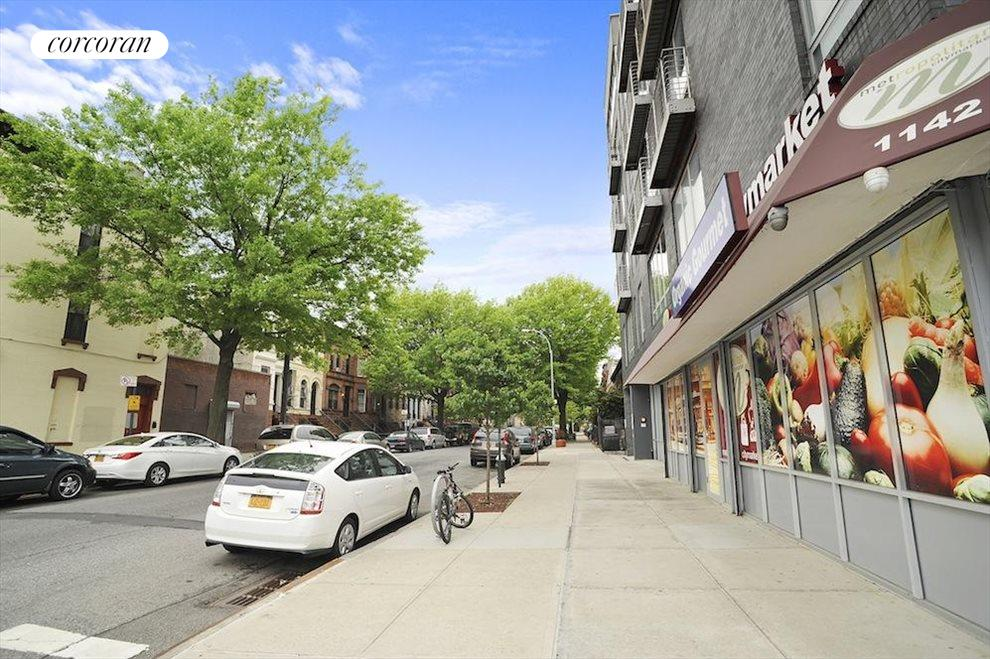 Beautiful tree-lined street with grocery on the co