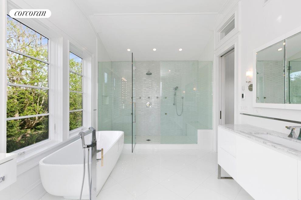 Soaking tub, rain shower and vanity in her bathroom