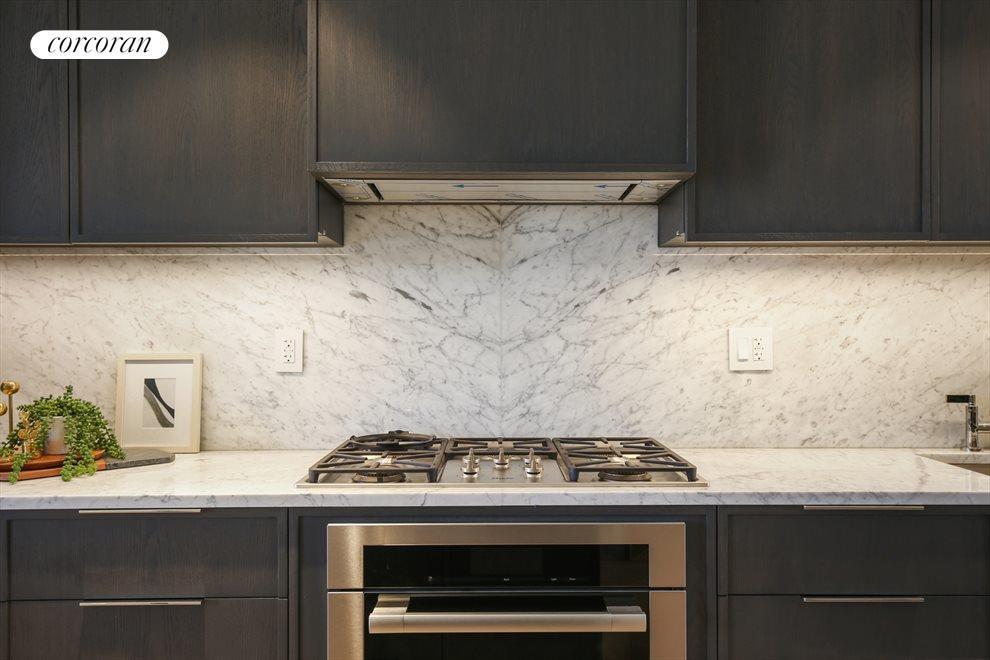 Bookatched marble backsplash and Miele appliances